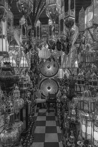 Traditional Moroccan decorative lamps hanging from shop ceiling in medina Marrakech